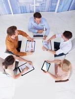 Geschäftsleute diskutieren auf Grafiken am Konferenztisch foto