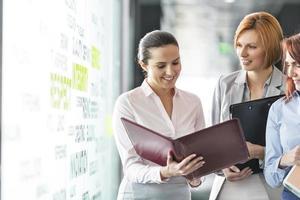Geschäftsfrauen mit Aktenordnern, die im Bürokorridor diskutieren