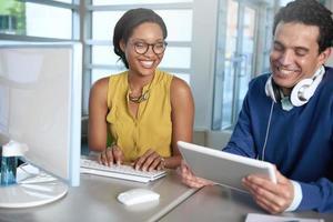 Zwei Kollegen diskutieren Ideen mit einem Tablet und einem Computer foto