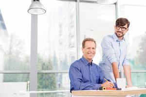fröhliche männliche Arbeiter diskutieren über den Bauplan foto