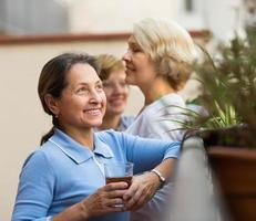 Drei Frauen trinken Tee auf dem Balkon foto