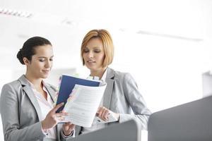 junge Geschäftsfrauen diskutieren über Buch im Büro foto