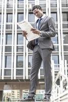 schwarzer Geschäftsmann, der Zeitung im Freien liest foto
