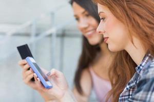 Studenten, die ihre Smartphones zusammen benutzen foto