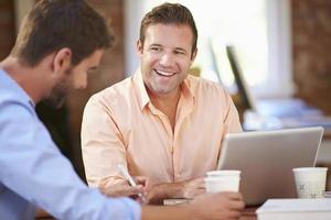 zwei Geschäftsleute, die zusammen am Schreibtisch arbeiten