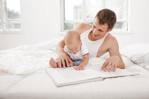 Vater und Baby lesen gemeinsam ein Buch foto