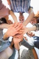 glückliche Schüler, die ihre Hände zusammenlegen foto
