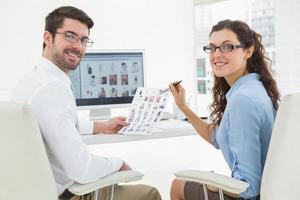 lächelnde Kollegen, die miteinander über Fotos interagieren