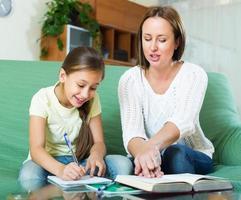 Mutter mit kleiner Tochter machen gemeinsam Hausaufgaben