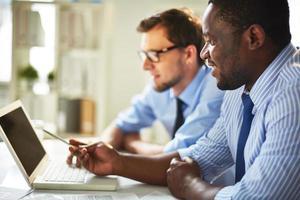 lächelnde Geschäftsleute, die zusammen einen Laptop betrachten foto