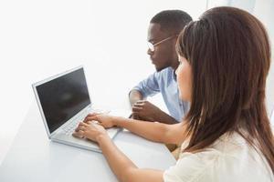 fokussierte Kollegen, die gemeinsam einen Laptop benutzen foto