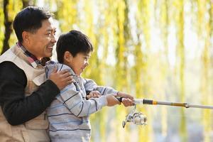 Vater und Sohn fischen zusammen am See foto