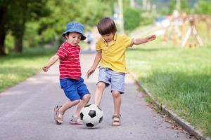 zwei süße kleine Kinder, die zusammen Fußball spielen, Sommerzeit