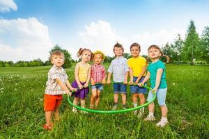 sechs lustige Kinder, die einen Reifen zusammenhalten foto