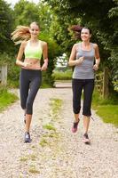 zwei Freundinnen laufen zusammen auf dem Land