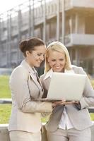 glückliche junge Geschäftsfrauen, die Laptop zusammen gegen Gebäude verwenden foto