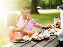 Vater und Tochter essen zusammen beim Grillen foto