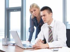 Geschäftsleute, die zusammen auf Laptop im Büro arbeiten foto