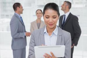 Geschäftsfrau mit ihrem Tablet-PC, während Kollegen miteinander sprechen foto