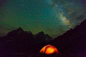 Nacht Berglandschaft mit beleuchtetem Zelt foto