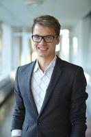 junger Geschäftsmann mit Gläsern, die im Flur stehen foto