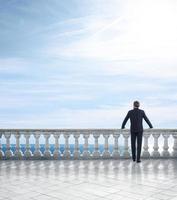 Geschäftsmann, der auf einer Terrasse mit Blick auf das Meer steht foto