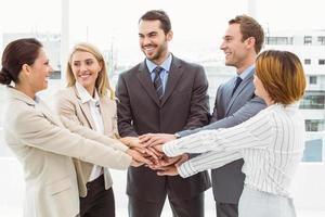 Führungskräfte, die im Amt die Hände zusammenhalten foto