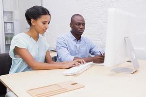 Geschäftsteam arbeitet zusammen auf Laptop