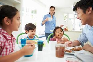 asiatische Familie, die zusammen in der Küche frühstückt foto