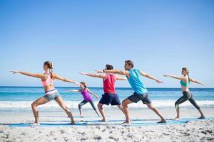 Freunde, die zusammen mit ihrem Lehrer Yoga machen foto