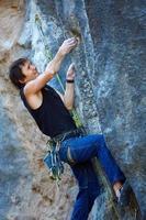 Kletterer klettert eine Klippe hinauf
