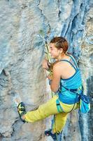 Kletterer klettert eine Klippe hinauf foto