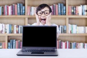 ausdrucksstarkes Kind mit Laptop, der in der Bibliothek schreit foto