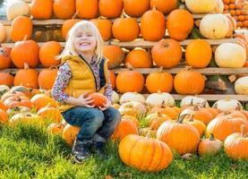 Porträt des glücklichen Kindes, das auf Kürbis sitzt foto