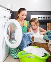 Frau mit Kind in der Nähe von Waschmaschine foto