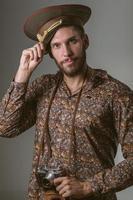 russischer Tourist, der militärischen Hut und Kamera trägt foto