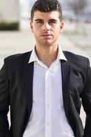 junger Geschäftsmann nahe einem Bürogebäude, das schwarzen Anzug trägt