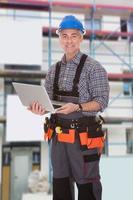Handwerker hält Laptop foto