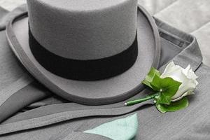 Herrenanzug, hoher Hut und Boutonniere foto