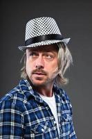 ausdrucksstarker junger Mann mit blonden langen Haaren und Skahut. foto