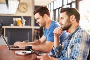 zwei junge Männer, die an Computern in einem Café arbeiten foto