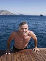 Mann kommt aus dem Wasser auf der Diele der Yacht foto