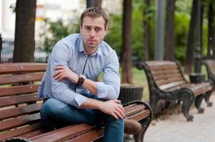 Mann, der sich in einem öffentlichen Garten entspannt, der auf einer Holzbank sitzt foto