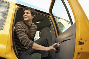 junger Mann, der Taxi aussteigt foto