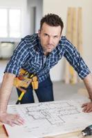 Porträt des schönen Bauarbeiters mit Hauptplänen foto