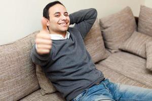 junger Mann, der auf Sofa sitzt und ok Zeichen zeigt foto