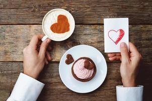 Männerhände halten eine Tasse Kaffee und eine Grußkarte foto