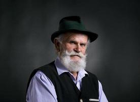 alter bayerischer Mann im Hut auf schwarzem Hintergrund