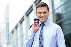 Geschäftsmann, der außerhalb des modernen Gebäudes steht foto