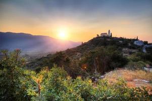 Sonnenuntergang auf einer Hügelkirche foto